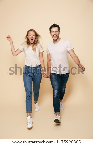 happy young loving couple walking isolated over beige wall background pointing stock photo © deandrobot