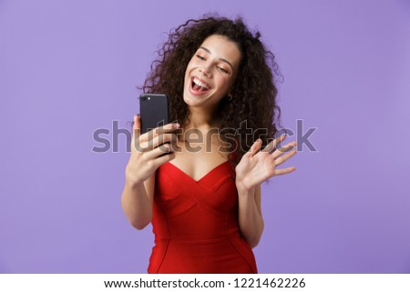 Image of joyous woman 20s wearing red dress using black smartpho Stock photo © deandrobot