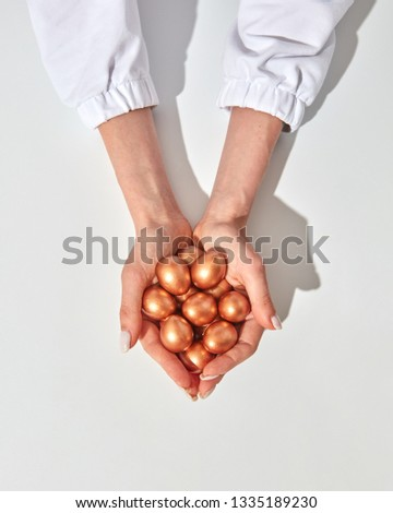 Close-up of a girl's hand holding many colored golden eggs against the background of a white apron.  Stock photo © artjazz