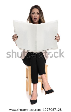 shocked businesswoman sits on wooden stool while holding newspap Stock photo © feedough