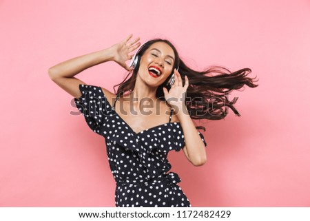 Pleased brunette woman in dress and headphones listening music Stock photo © deandrobot