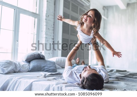 Happy father and daughter having fun together on a bed ストックフォト © Lopolo