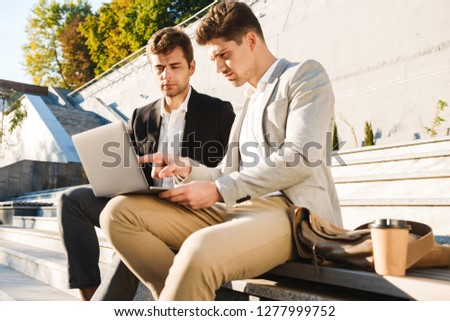 Photo of mature businessmen in suits sitting on staircase outdoo Stock photo © deandrobot