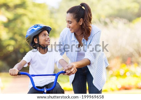 Young mother teaching her son how to ride a bicycle in the park Stock photo © galitskaya
