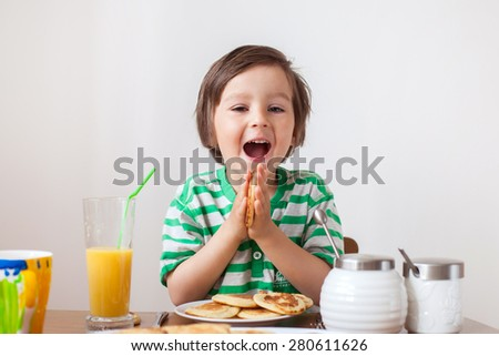 sweet little caucasian boy eating pancakes and drinking orange juice stock photo © galitskaya