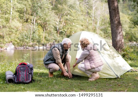 Mature hikers in activewear putting tent on green grass by riverside Stock photo © pressmaster