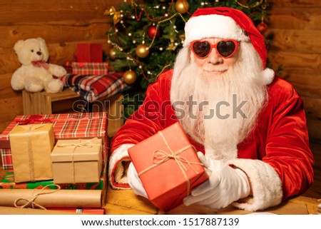 Santa in costume, white gloves and heartshaped sunglasses holding red giftbox Stock photo © pressmaster