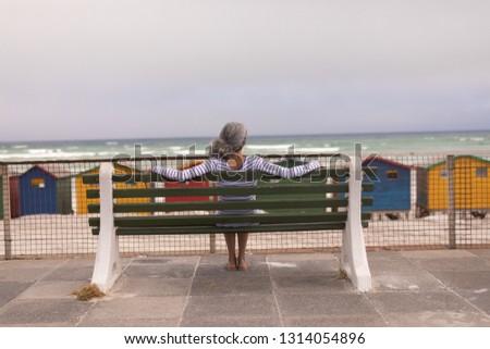 Vue arrière supérieurs femme séance promenade banc Photo stock © wavebreak_media
