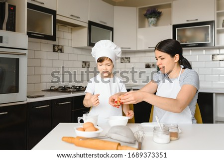 Happy mother and her little son shaking raw eggs in bowl before making dough Stock photo © pressmaster