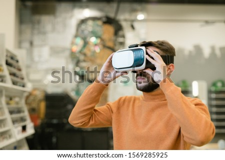 Bearded young man wearing vr headset inside contemporary optics shop Stock photo © pressmaster