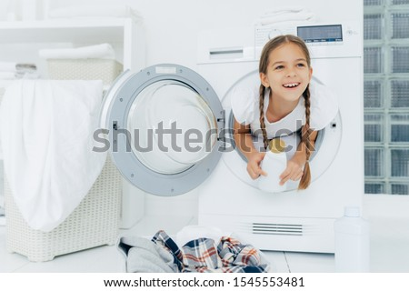 Happy European girl with two plaits, poses inside of wash machine, holds white bottle with liquid po Stock photo © vkstudio