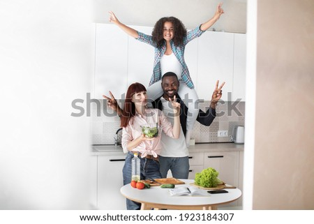 Happy parents cook together with daughter, pose at modern home kitchen give eggs to add to dough, sm Stock photo © vkstudio