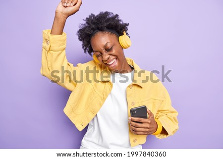 Smiling millennial girl with Afro hair, enjoys cellphone conversation with hot drink in cup, has hea Stock photo © vkstudio