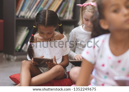 Surface level view of mixte ethnicity schoolgirls holding digital tablet and sitting on cushions in  Stock photo © wavebreak_media