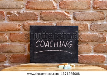 Chalk board with the word COACHING drown by hand on wooden table Stock photo © marylooo