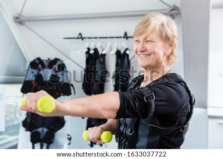 Senior lady staying fit with dumbbell exercise in wireless ems gym Stock photo © Kzenon