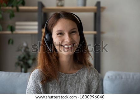 Close up shot of happy young European woman has pleasant smile, keeps hands together near chin, wear Stock photo © vkstudio