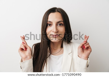 Photo of happy businesswoman crosses fingers for good luck, believes everything will be fine, prays  Stock photo © vkstudio