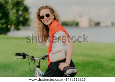 Satisfied curly female bicyclist enjoys spare time, travels on bike, stops to have little rest, wear Stock photo © vkstudio