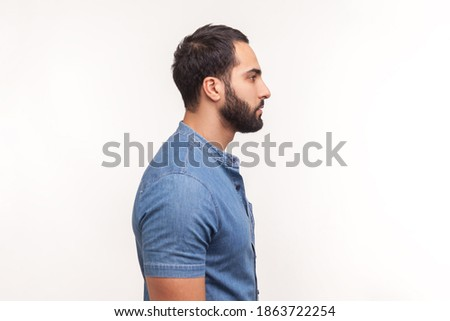 Studio shot of self assured bearded man with blue eyes, wears stylish hat and white shirt, keeps arm Stock photo © vkstudio