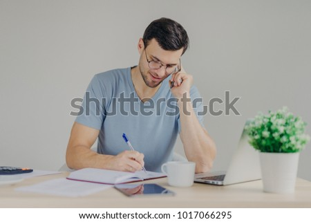 Serious brunet young male sits in front of opened laptop, talks on mobile phone and writes down note Stock photo © vkstudio