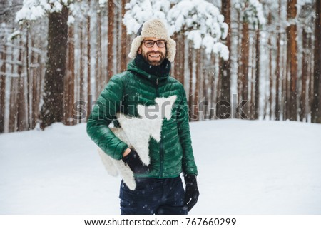 Cheerful bearded male wears warm anorak and hat, walks in winter forest, holds artificial fir tree,  Stock photo © vkstudio