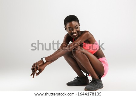 Image of african american sportswoman using earbuds while sitting Stock photo © deandrobot