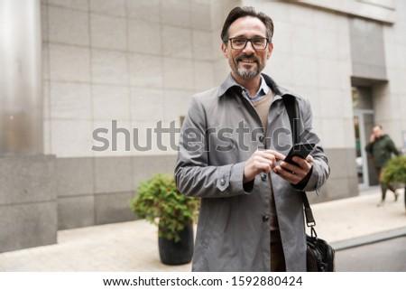 画像 成熟した あごひげを生やした ビジネスマン 携帯電話 徒歩 ストックフォト © deandrobot