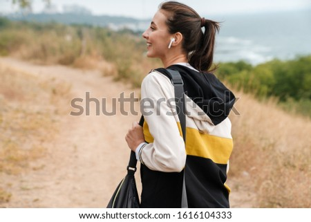 Photo of nice laughing woman using earpods while working with bag Stock photo © deandrobot