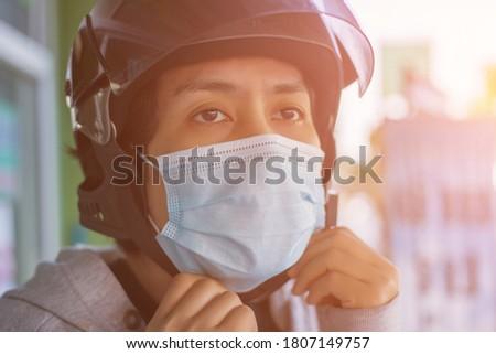 Man wearing medical mask and riding a scooter Coronavirus pandemic Covid-19. Sport, Active life in q Stock photo © galitskaya
