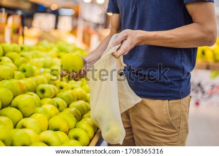 Man chooses tomatoes in a supermarket without using a plastic bag. Reusable bag for buying vegetable Stock photo © galitskaya