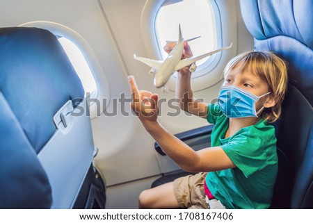 Little boy in medical mask play with toy plane in the commercial jet airplane flying on vacation Tou Stock photo © galitskaya
