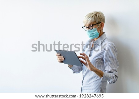 Mature businesswoman using a handheld tablet and wear mask to pr Stock photo © boggy