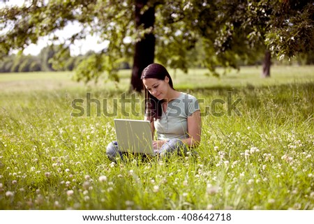 Woman sitting crossed legged in front of tree using laptop computer Stock photo © photography33