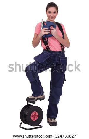 Tradeswoman holding a jigsaw with her foot propped on an extension reel Stock photo © photography33