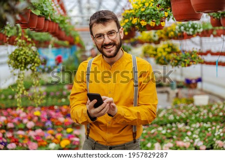 Woman gardener standing over plants in greenhouse take a selfie by camera. Stock photo © deandrobot
