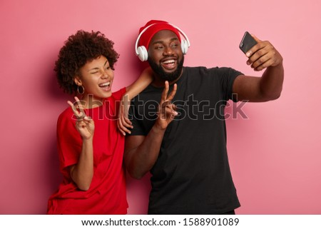 Photo of joyous hipsters men and women smiling, and taking selfi Stock photo © deandrobot
