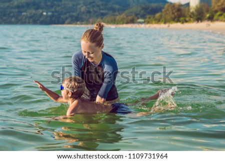 Woman swimming instructor for children is teaching a happy boy to swim in the pool Stock photo © galitskaya