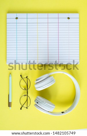 Headphones, eyeglasses, pen and lined page of notebook over yellow background Stock photo © pressmaster