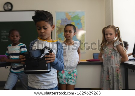 Front view of schoolboy holding and looking at virtual reality headset with his classmates who look  Stock photo © wavebreak_media