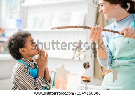 Cute boy with pleading expression and gesture looking at woman with xmas toys Stock photo © pressmaster