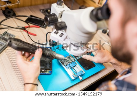 Hands of repairman with electric handtool looking in microscope during work Stock photo © pressmaster