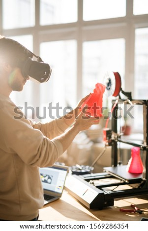 Young businessman in vr headset holding red plastic object in front of himself Stock photo © pressmaster
