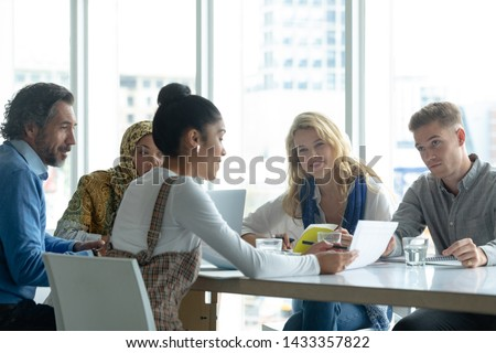 front of view of diverse business people discussing over documents at table after a seminar in offic stock photo © wavebreak_media