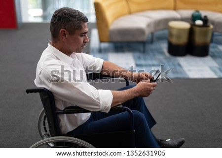 Side view of mature Causasian disabled businessman using mobile phone while sitting on wheelchair in Stock photo © wavebreak_media