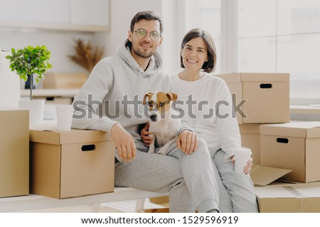 Positive woman and man pose near stack of cardboard boxes, pose for making portrait with dog, reloca Stock photo © vkstudio
