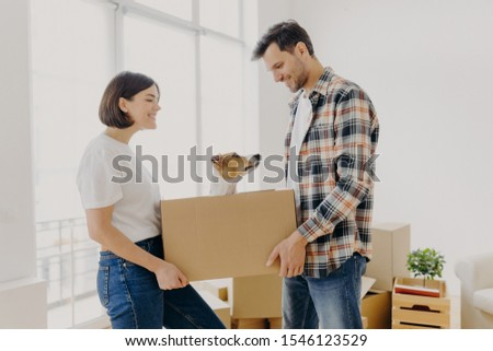 Satisfied lovely family couple carry carton box with their domestic pet, move in new dwelling prepar Stock photo © vkstudio