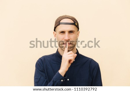 Horizontal shot of handsome young male model keeps fore finger on lips, asks to be quiet, wears cap  Stock photo © vkstudio