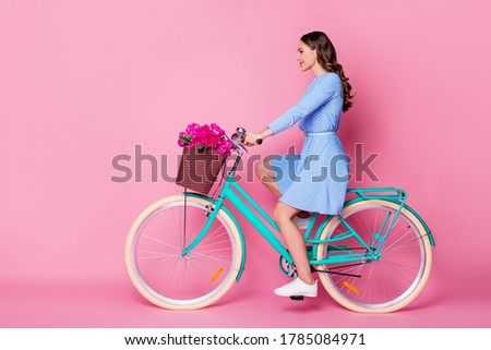 Active cheerful woman rides bicycle in city, wears stylish sunglasses, has toothy charming smile, dr Stock photo © vkstudio
