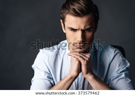 Calm and handsome. Portrait of handsome young man keeping hands clasped and looking thoughtful. Stock photo © benzoix